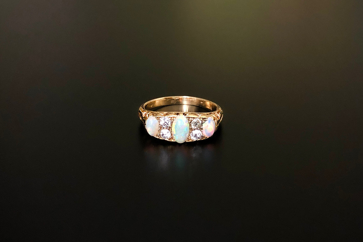 A Petite Opal and Diamond Ring Carved half hoop set with three graduating oval opals interspaced with four small old cut diamonds Approximate diamond weight: 0.16cts 18ct yellow gold Victorian Total weight: 3.5gms
