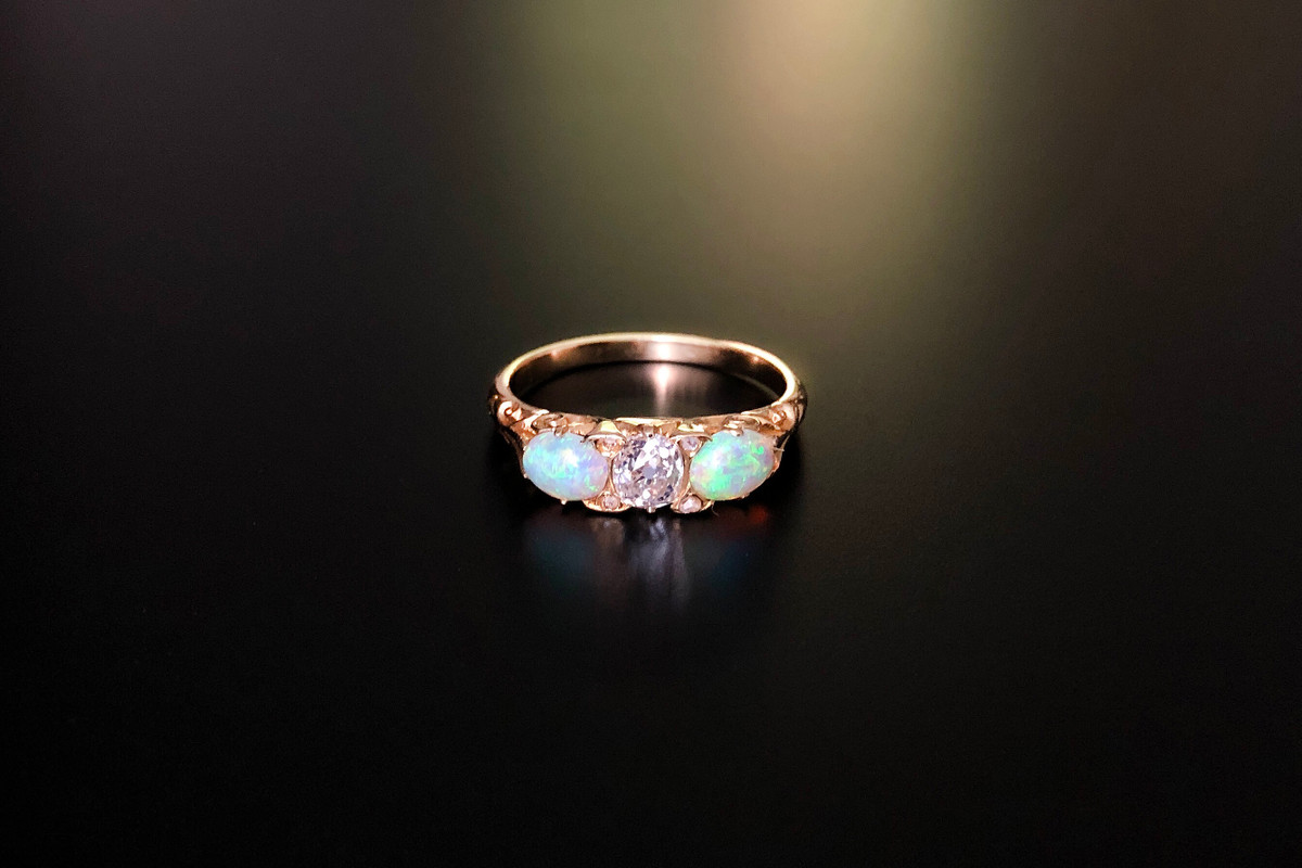 A Luminous Diamond and Opal Ring Carved half hoop set with a central old brilliant cut diamond With an oval opal set sideways to each shoulder Interspaced with four small rose cut diamonds set into the claws Approx diamond weight: 0.47cts. 18ct yellow gold Victorian Total weight: 3.30gms