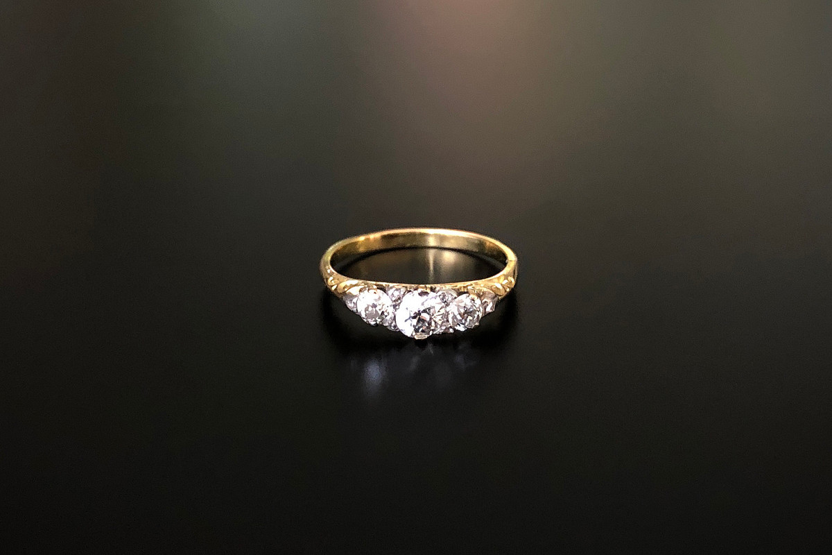 A Delicate Three Stone Diamond Half Hoop Ring. Carved scroll design  With three old brilliant cut diamonds  Interspaced with six small rose cut diamonds set into the claws Approx diamond weight: 0.75cts 18ct yellow gold Victorian Size: P