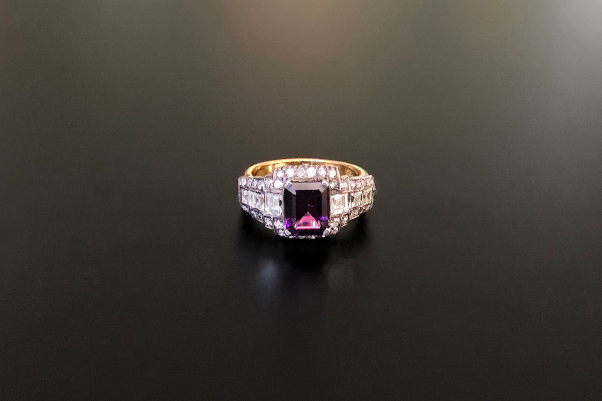 A Stylish Amethyst and Diamond Ring, Set with a central emerald cut amethyst With graduating square cut diamonds to the shoulders Surrounded with single cut diamonds  Amethyst weight: 1.50cts Approx diamond weight: 1.46cts 18ct yellow and white gold setting Total weight: 6.09gms Vintage.