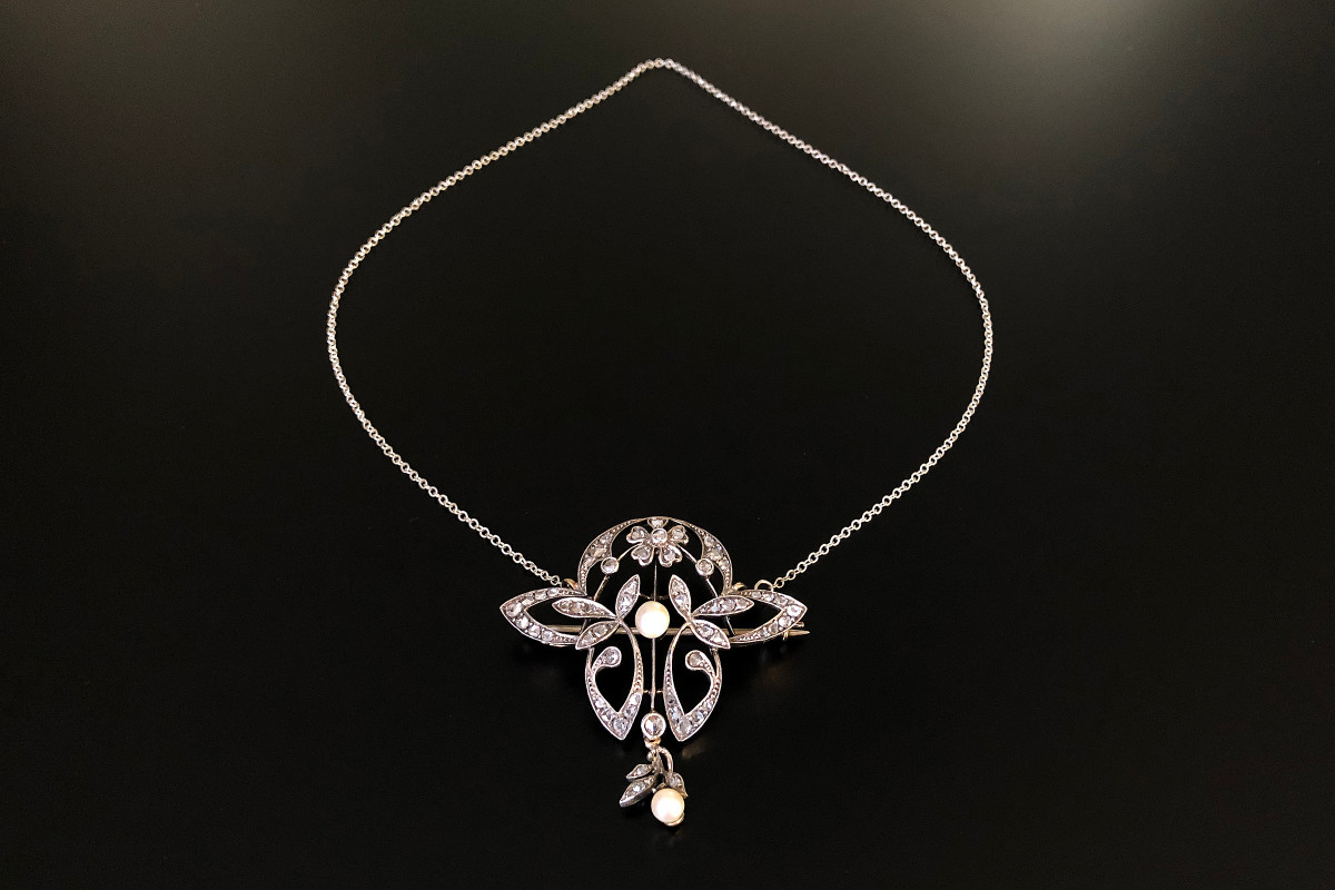 An Elegant Diamond and Pearl Brooch Pendant Open form with foliate and flower motif set with rose cut diamonds and a central natural pearl,  Suspending a smaller natural pearl with further foliate details. Brooch pin to the reverse. On a belcher link chain. Total weight: 13.09gms Dimensions: 50 x 55mm Chain length: 500mm c1910.