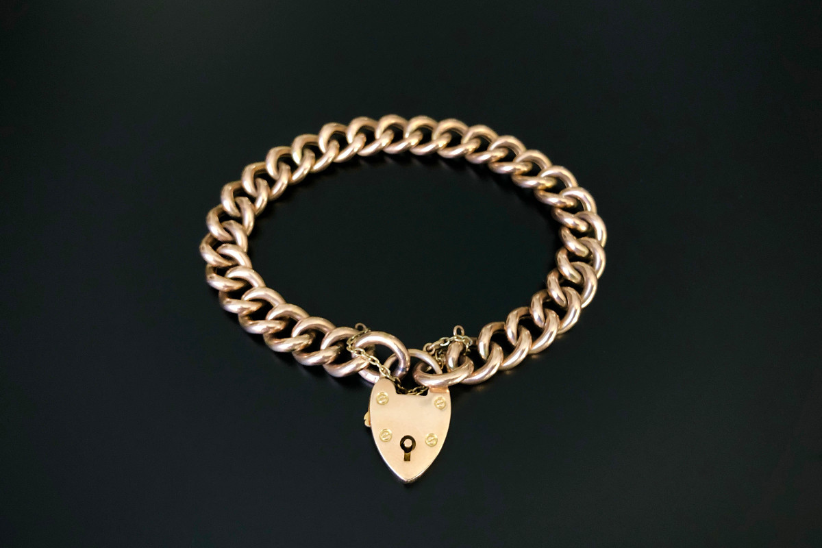 A Classic Gold Curb Link Bracelet Hollow rose gold links finished with two jump rings, heart padlock and safety chain 15ct gold Total weight: 26.5gms Victorian Circa 1890