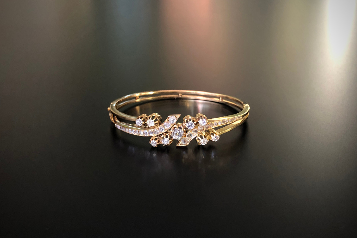 A Stylish Diamond Hinged Bangle. Double cross over design with nine Old Brilliant Cut diamonds individually claw set With a further twenty eight graduated rose cut diamonds to the split setting With safety chain Approx diamond weight: 0.45cts Total weight: 19.49gms 18ct yellow gold French 19th century