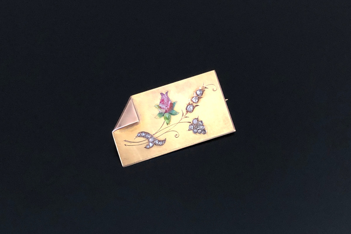 A Unique Enamel and Diamond Brooch Gold rectangular form with a folded corner decorated with an enamelled rose and carved floral motifs set with old rose cut diamonds. Total weight: 8.72gms 15ct yellow gold