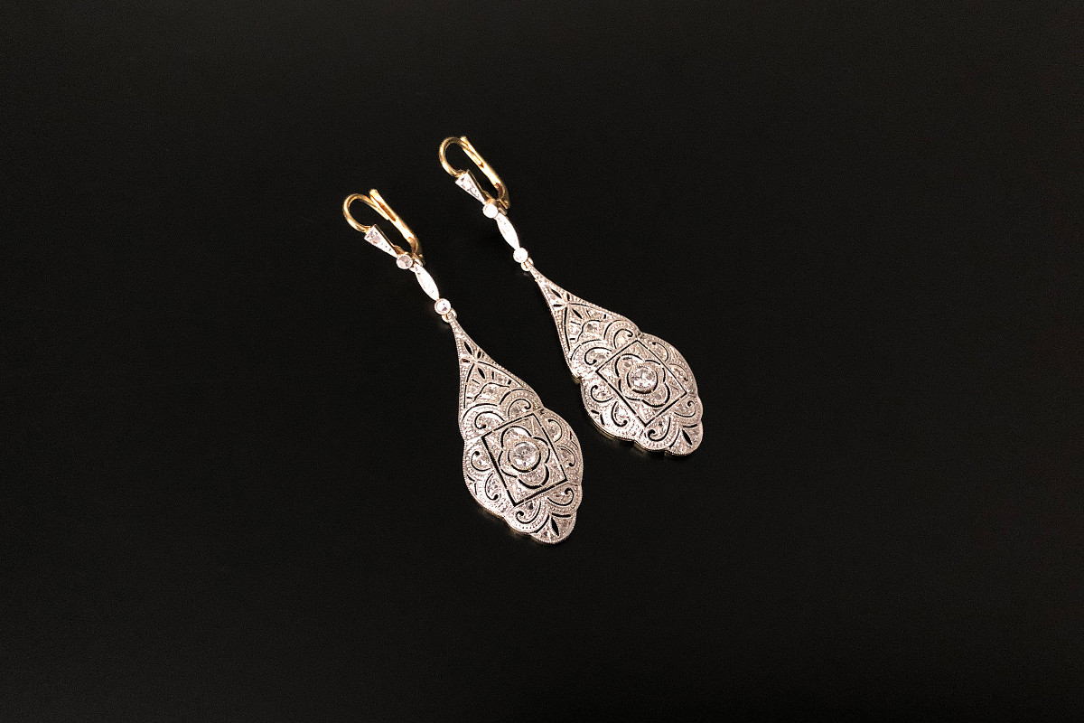 A Sophisticated Pair of Diamond Pendant Earrings  Finely pierced and stylised pear shaped form Each set with one small old brilliant cut diamond and fourteen small rose cut diamonds Approximate total diamond weight: 0.35cts 18 carat yellow and white gold setting Total weight: 6.45gms c1920