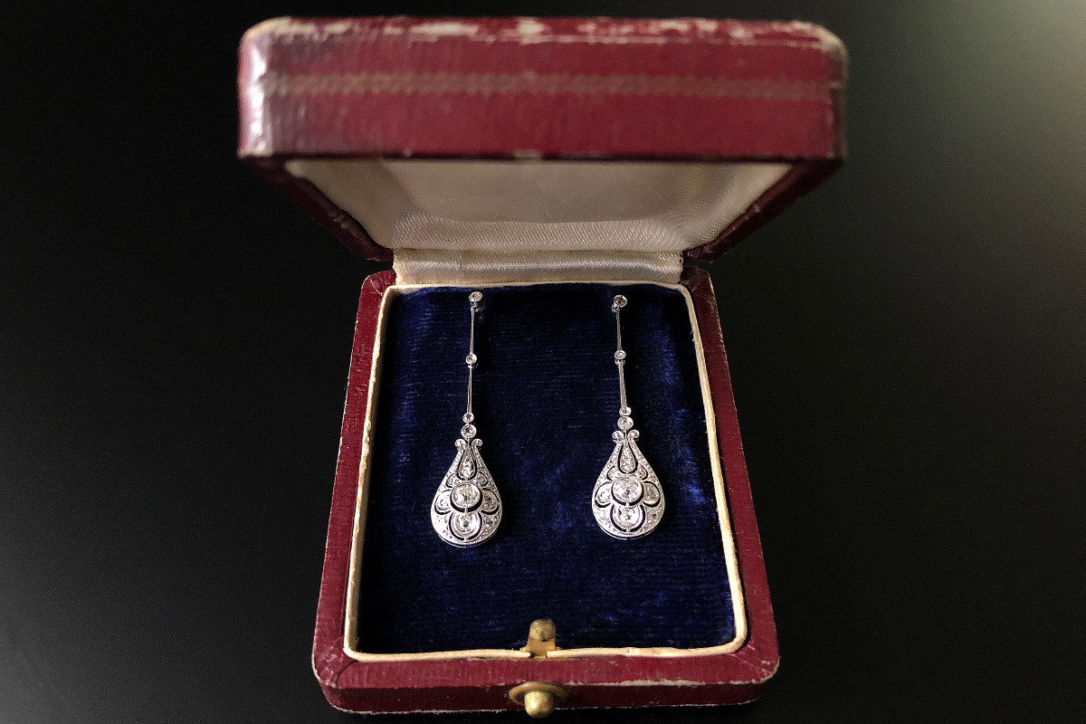 An Elegant Pair of Diamond Pendant Earrings. Pierced and stylised pear shaped pendant  Set with one old cut diamond and surrounded with rose cut diamonds.  Suspended from fine articulated sections set with four small rose cut diamonds Approximate total diamond weight: 0.35cts Total weight: 4.22gms Total length: 40mm 18ct white gold setting. Edwardian.