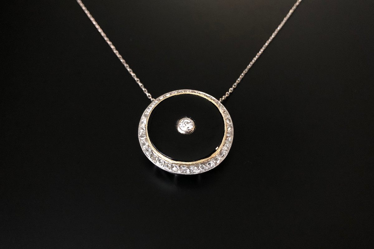 A Gorgeous Circular Onyx and Diamond Pendant Comprising of a central Old Brilliant Cut diamond set within a circular polished onyx panel framed by a border of rose cut diamonds. Approx central diamond weight: 0.25cts 18ct yellow and white gold setting Total weight: 9.62gms Dimensions: 28 x 28mm c1900