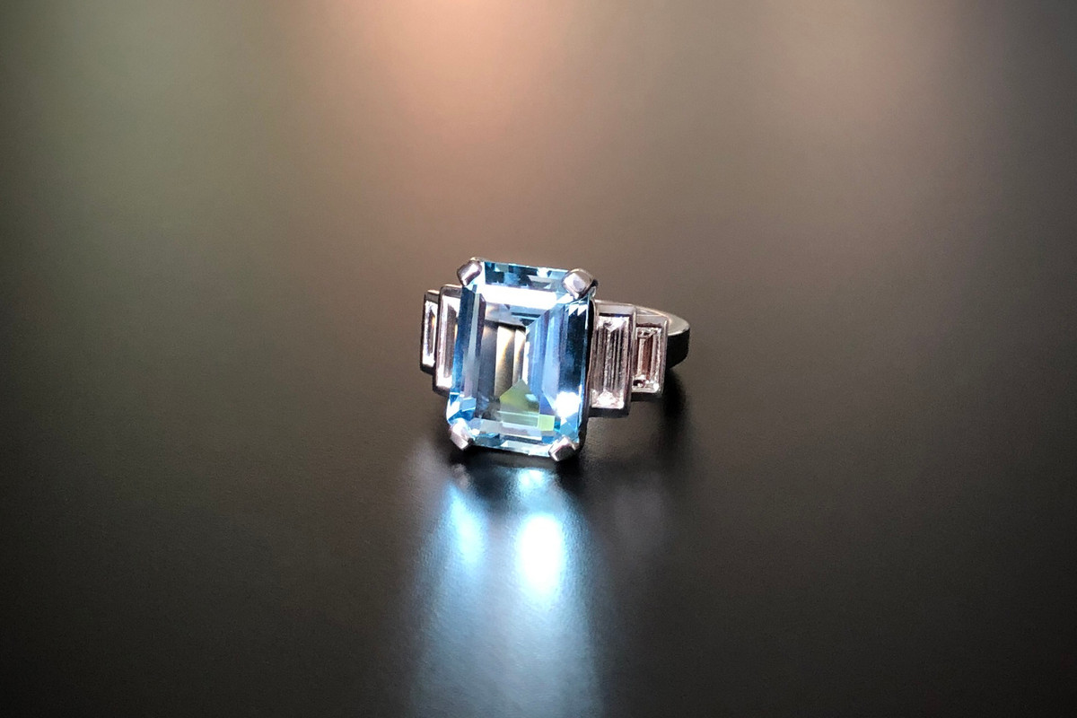 A Stunning Kozminsky Aquamarine and Diamond Ring Comprising an Emerald Cut aquamarine, basket set with four claws Accompanied with two graduating Baguette Cut diamonds, bezelled set to the shoulders. Aquamarine weight: 6.03cts Total diamond weight: 1.05cts, E-F, VVSI-VSI Total weight: 10.77gms 18ct white gold Size: M