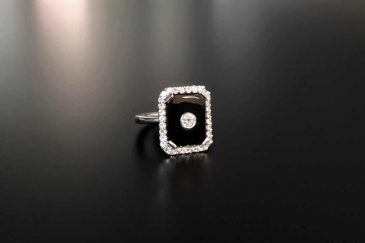 A Divine Onyx and Diamond Plaque Ring Centrally set with an old cut diamond within a rectangular polish onyx plaque panel Surrounded by a border of small old cut diamonds 18ct white gold Total diamond weight: 0.77cts Colour: G  Clarity: SI Total weight: 9.7gms Size: L1/2