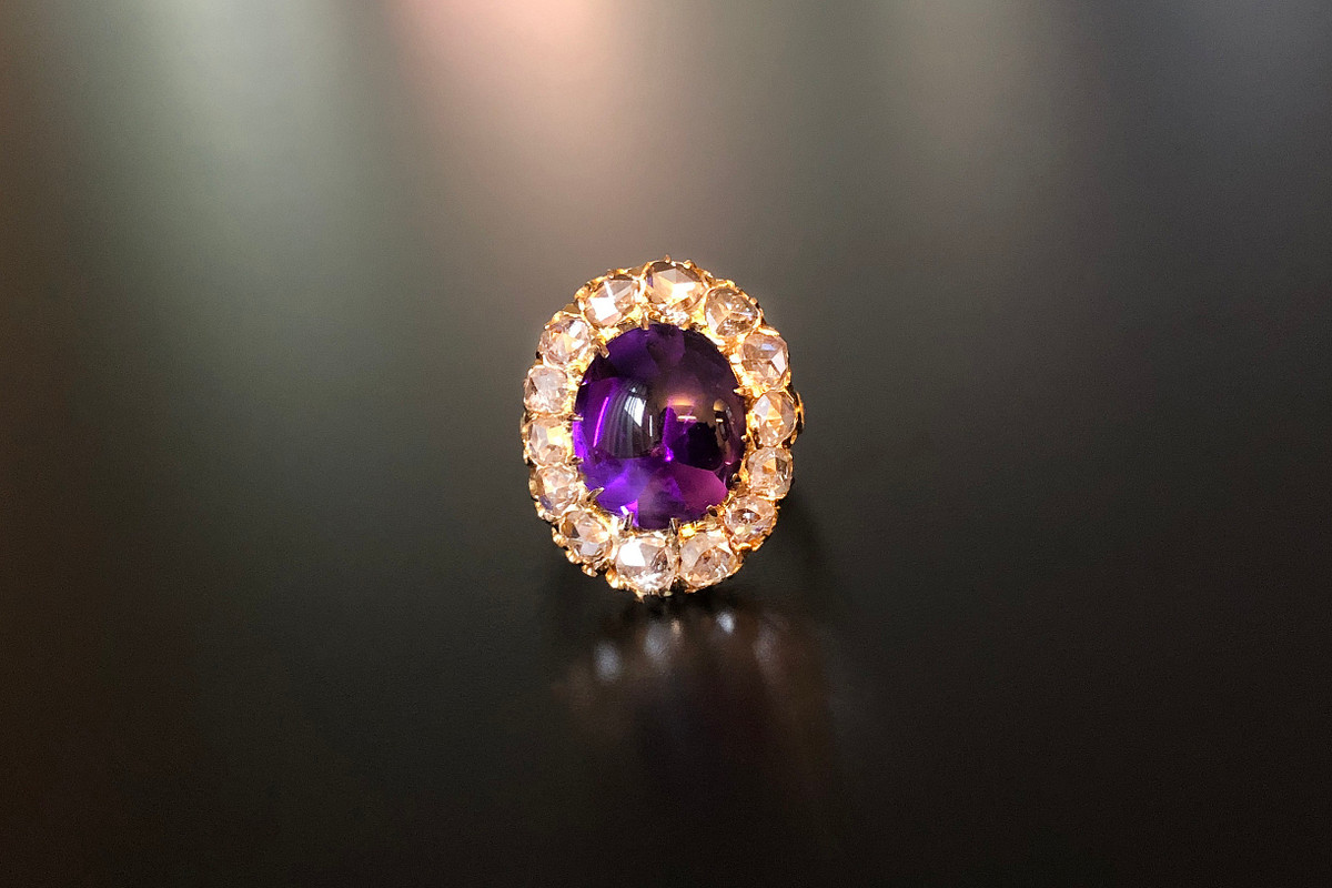 A Beautiful Amethyst and Diamond Ring Oval amethyst cut en cabochon Surrounded by fourteen old rose cut diamonds Approximate amethyst weight: 13.20cts Approximate total diamond weight: 1.50cts Total weight: 5.69gms 9ct yellow gold Size: M