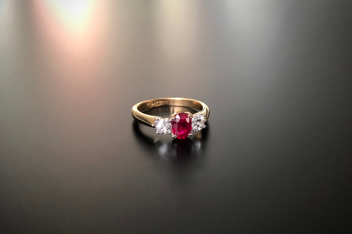A Classic Three Stone Ruby and Diamond Ring Comprising a central oval Burmese Ruby with an Old Brilliant Cut diamond to the shoulders. Ruby weight: 1.01cts Total diamond weight: 0.42cts, J-K, SI. Claw setting 18ct yellow gold. Total weight: 3.95gms Size: M1/2