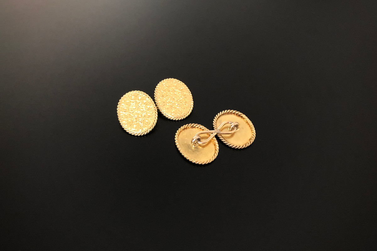 A Pair of Gold Cufflinks Oval design with chased floral decoration and rope twist border. 15ct yellow gold. Dimensions: 20 x 16mm Total weight 6.0gms.