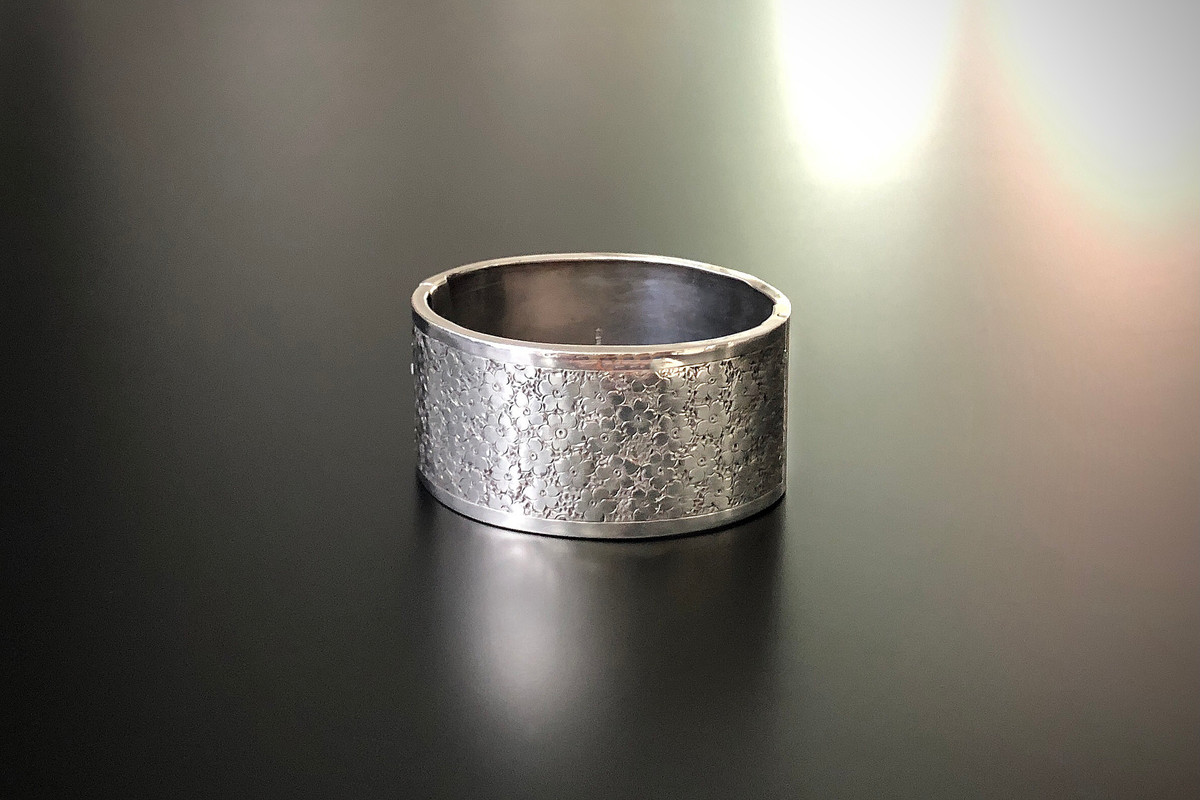 A Victorian Silver Bangle Oval hinged form The front panel finely hand engraved with a garden of flowers Sterling silver.  Birmingham 1882. Dimensions: 30 x 58mm Total weight: 32.78gms