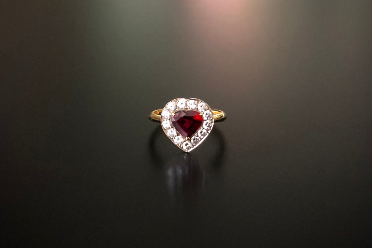 A Darling Ruby and Diamond Cluster Ring Comprising a central heart-shaped ruby surrounded by round brilliant cut diamonds. Approximate ruby weight: 1.19cts Approximate diamond weight: 0.39cts. Diamond colour: H-I. Diamond clarity: SI. Claw and fine millegrain setting. 18ct yellow gold.