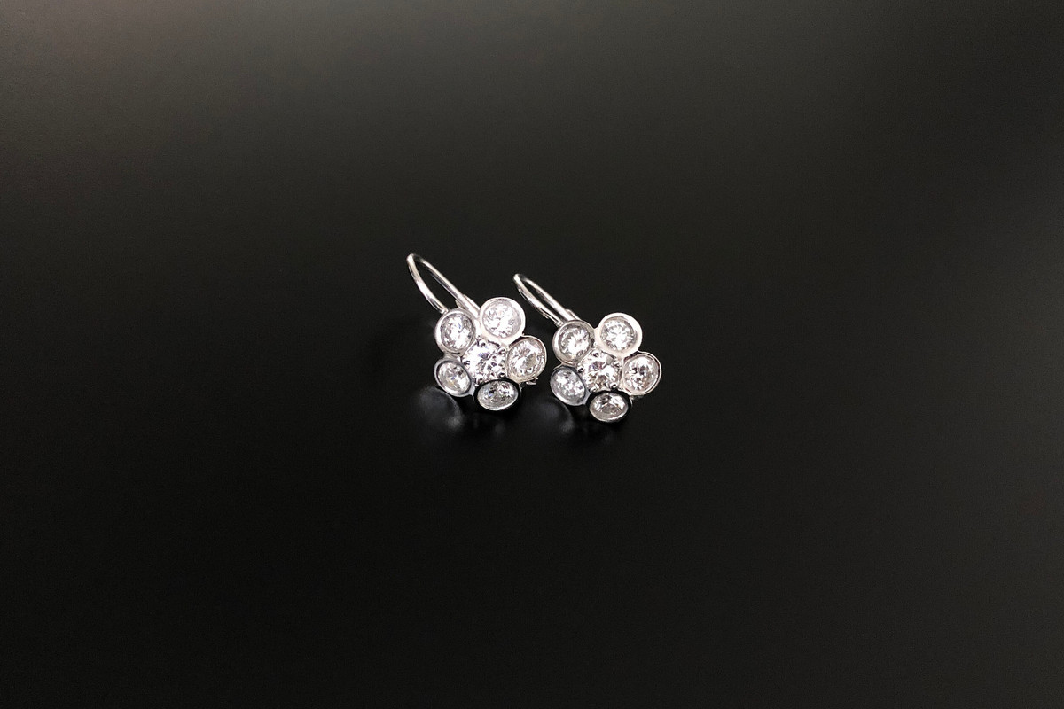 A Lovely Pair of Diamond Cluster Earring Flower form, with five Round Brilliant Cut diamonds as  petals in a rubbed-in setting. Surrounding a Round Brilliant Cut diamond, to the centre. European hook fittings. Approximate total diamond weight: 2.07cts Diamond colour: J Diamond clarity: SI1 Platinum and 14ct white gold. Total weight: 4.90gms Dimensions: 16 x 12mm