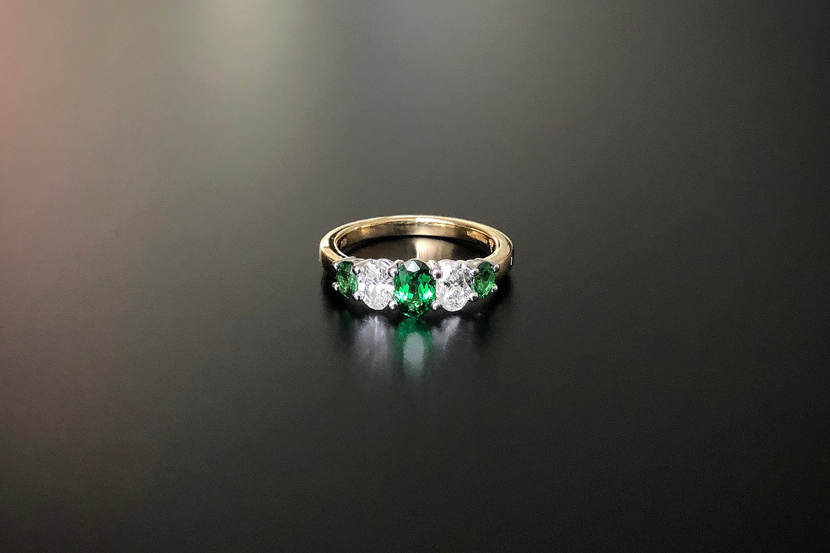 A Stunning Kozminsky Oval Tsavorite and Diamond Ring Comprising three oval tsavorite graduating in size, interspaced by two oval cut diamonds in a half hoop design. Total diamond weight: 0.60cts, G, SI Total Tsavorite weight: 0.91cts, Grade 2. 18ct yellow gold band with white gold setting. Total weight: 4.33gms Size: N