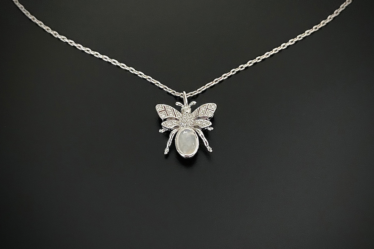 Kozminsky 170th Year Silver Bee Pendant with Moonstone. Set with an oval cabochon moonstone body with diamond set wings. Two small cabochon moonstone for eyes. Moonstone weight: 0.91ct Total diamond weight: 0.10cts Sterling silver. Dimension: 15mm x15mm Sterling silver chain: 50cm