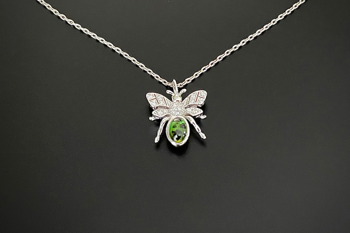 Kozminsky 170th Year Silver Bee Pendant with Green Garnet . Set with an oval cabochon garnet body with diamond set wings. Two small cabochon garnet for eyes. Green garnet weight: 0.91ct Total diamond weight: 0.10cts Sterling silver. Dimension: 15mm x 15mm Sterling silver chain: 50cm