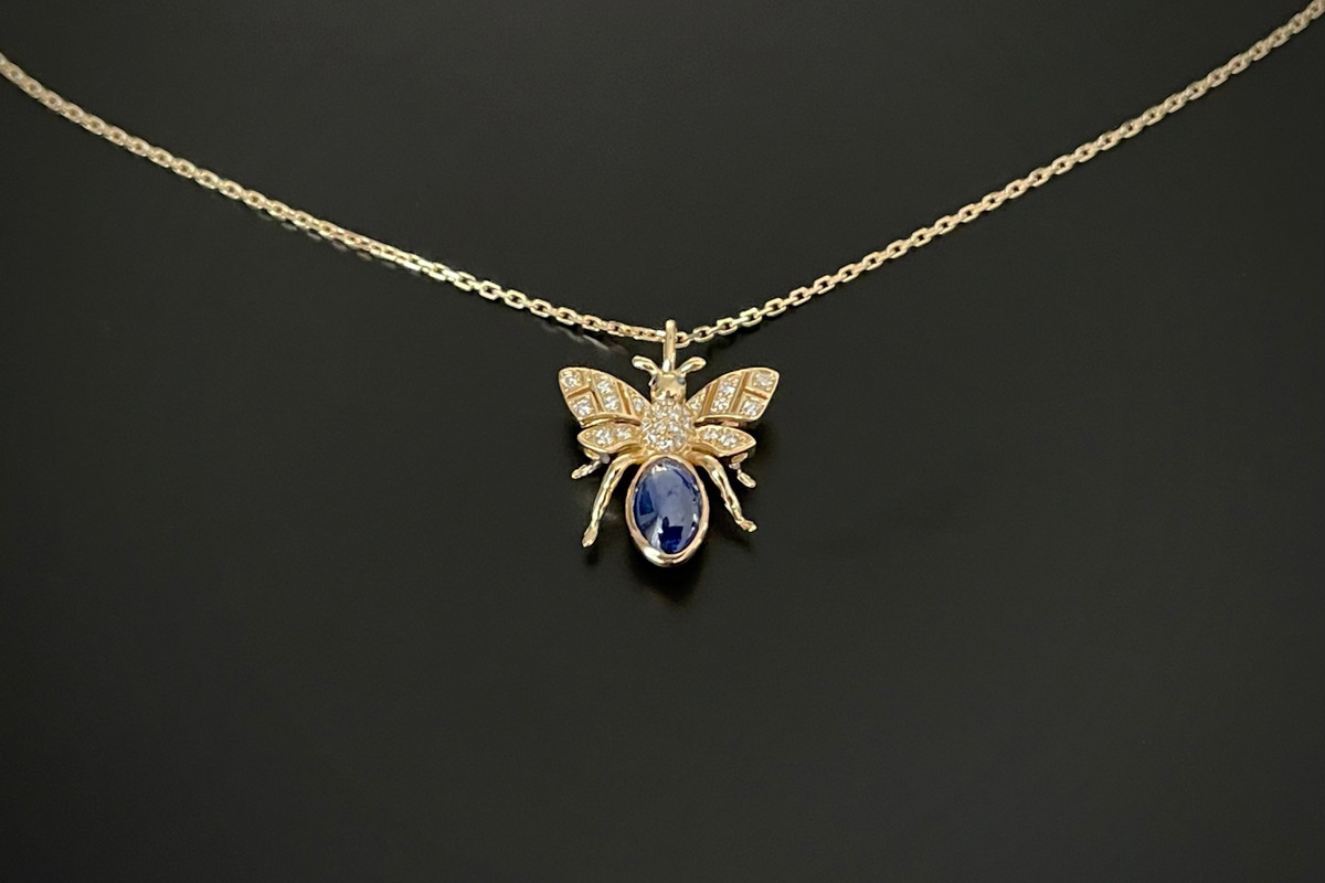 Kozminsky 170th Year Bee Pendant in Sapphire. Set with an oval cabochon sapphire body with diamond set wings. Two small cabochon sapphires for eyes. Sapphire weight: 1.71cts Total diamond weight: 0.10cts 18ct yellow gold. Fine trace link adjustable chain: 50cm