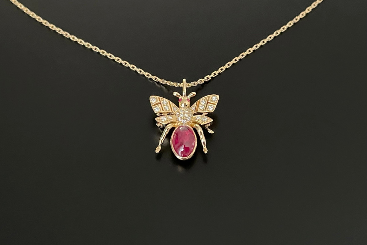 Kozminsky 170th Year Bee Pendant in Ruby. Set with an oval cabochon ruby body with diamond set wings. Two small cabochon rubies for eyes. Ruby weight: 1.33cts Total diamond weight: 0.10cts 18ct yellow gold. Fine trace link adjustable chain: 50cm