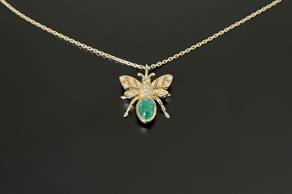 Kozminsky 170th Year Bee Pendant in Emerald. Set with an oval cabochon emerald body with diamond set wings. Two small cabochon emeralds for eyes. Emerald weight: 0.87ct Total diamond weight: 0.10cts 18ct yellow gold. Fine trace link adjustable chain: 50cm. Dimenssion: 15mm x15mm.