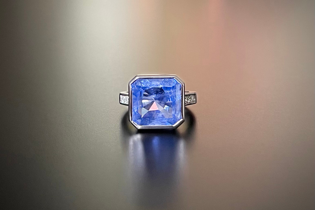 A Divine Sapphire and Diamond Ring Consisting of an Asscher Cut Natural Ceylon Sapphire, set with three small Princess Cut diamonds to each shoulder. Bezel set in 18ct white gold. Total sapphire weight: 13.10cts (12.91x12.99x7.43) Total diamond weight: 0.45cts. F-G, VS2. 18ct white gold band. Size: L1/2