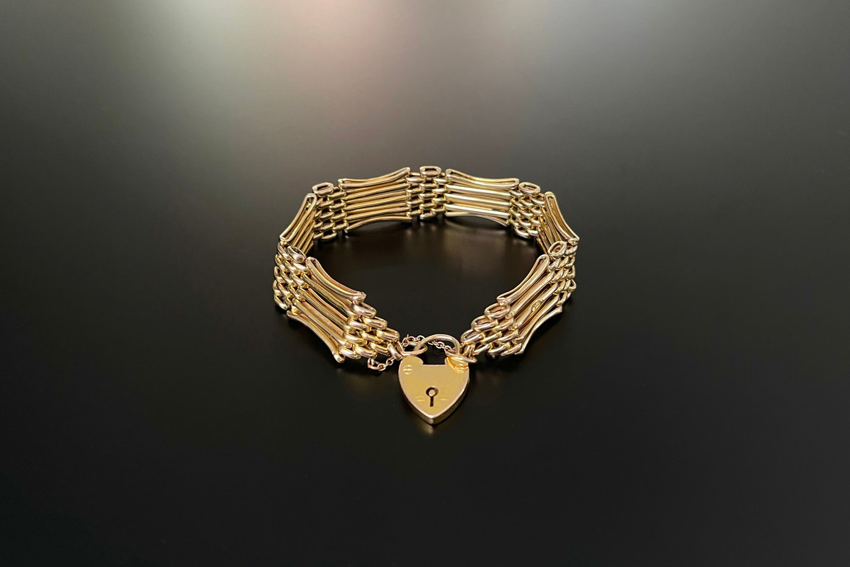 A Beautiful Fancy Link Bracelet Gate-link panels with concave borders, interspaced with articulated brick work design. With heart padlock and safety chain. 9ct yellow cold. Stamped: NBs