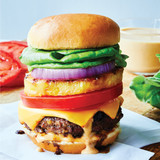 hamburger stacked tall with  slice of pineapple