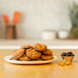 chocolate chip macadamia nut cookies on a plat next to chocolates and macadamia