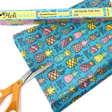 Image of Organic Cotton Beeswax Food wrap Bulk Roll with Multi colored pineapple pattern on blue background with scissors and bulk roll box