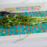 Image of Organic Cotton Beeswax Food wrap with Multi colored pineapple pattern on blue background under a small stack of parsley