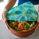 image of Organic Cotton Beeswax Food wrap with Tropical Green Leaf pattern on Pink background covering wooden salad bowl