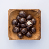 Island Harvest Organic Macadamia Nuts Covered in Dark Chocolate inside of a Wooden Bowl