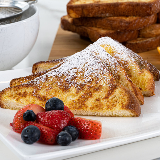 Delectable slices of french toast made with King's Hawaiian French Toast Batter Mix 8oz and King's Hawaiian Original Hawaiian Sweet Sliced Bread 12oz, dusted with powdered sugar