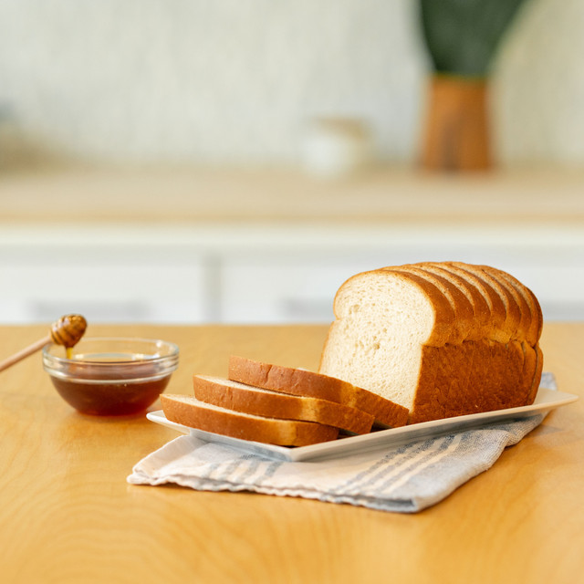 honey wheat loaf on a plate next to honey