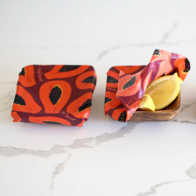 Image of Organic Cotton Beeswax Food wrap with Orange and Black papaya pattern on purple background covering one small bowl fully and half covering a bowl with yellow lemons