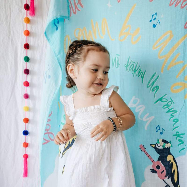 Female Child in white dress standing in front of Blue Coco Moon Hawaii Three little birds swaddle