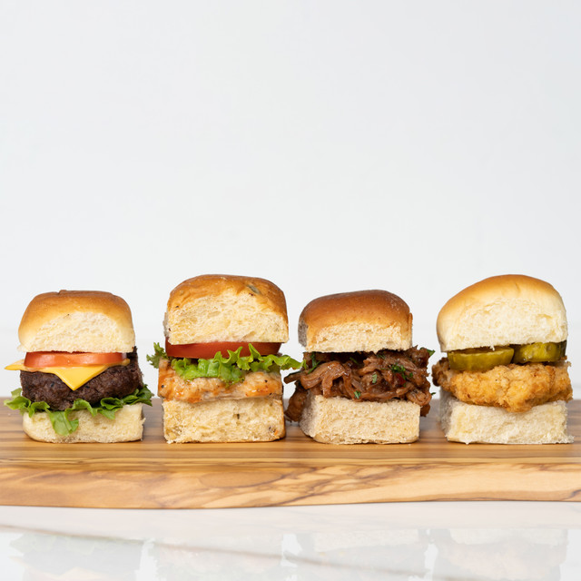 Delicious board of slider sandwiches made with King's Hawaiian Original Hawaiian Sweet Rolls 12ct, King's Hawaiian Jalapeño Rolls 12ct, King's Hawaiian Savory Butter Rolls 12ct, and King's Hawaiian Honey Wheat Rolls 12ct