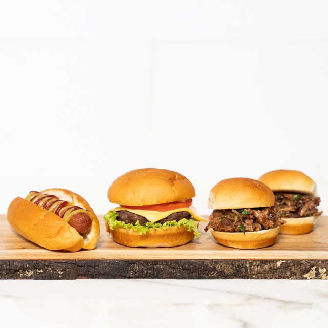 Platter of irresistible grill favorites made with King's Hawaiian Original Hawaiian Sweet Hamburger Buns 8ct, King's Hawaiian Original Hawaiian Sweet Hot Dog Buns 8ct, and King's Hawaiian Original Hawaiian Sweet Slider Buns (Pre-Sliced) 9ct