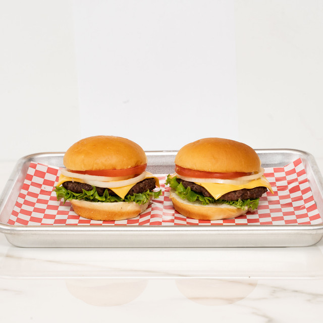 Two juicy and delicious cheeseburgers made with King's Hawaiian Original Hawaiian Sweet Hamburger Buns 8ct