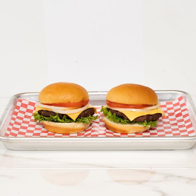 Two juicy and delicious cheeseburgers made with King's Hawaiian Original Hawaiian Sweet Hamburger Buns 8ct