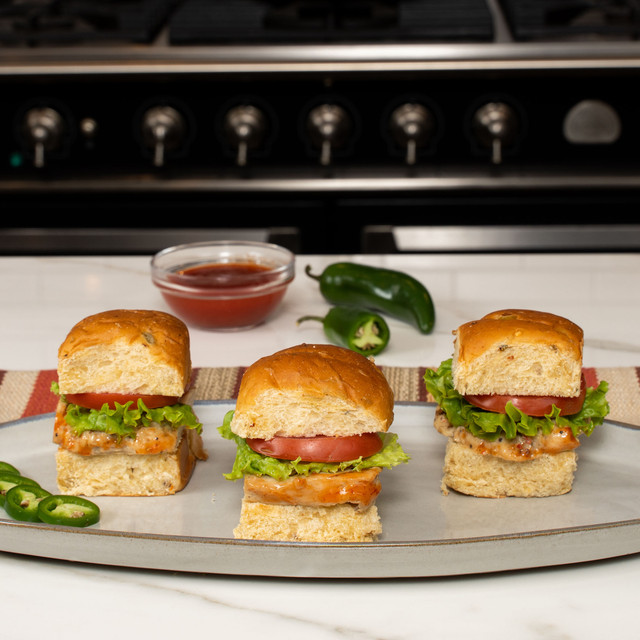 Trio of delicious chicken sliders on King's Hawaiian Hawaiian Sweet Jalapeño Rolls 12ct and topped with King's Hawaiian Big Island Lava Sauce 15oz
