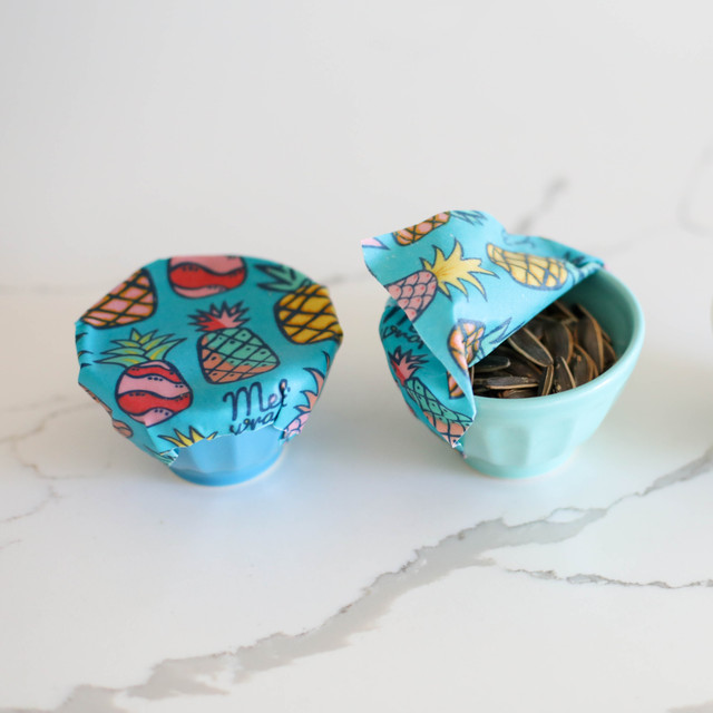 mage of Organic Cotton Beeswax Food wrap with Multi colored pineapple pattern on blue background Covering one small bowl fully and a second bowl half open with sunflower seeds