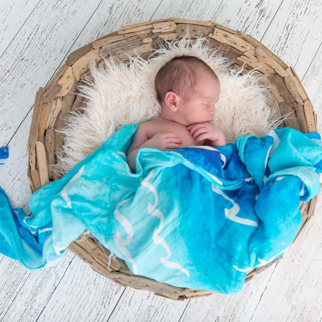 Sleeping baby in basket swaddled in Coco Moon hawaii Nalu baby Swaddle
