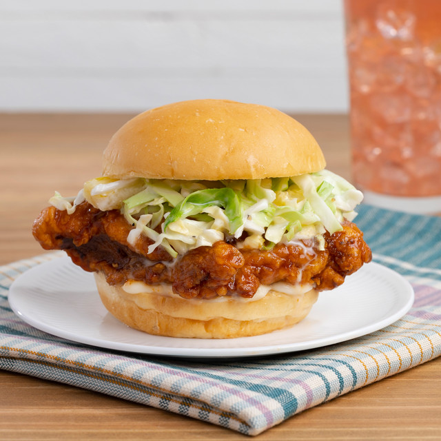 Image of Fried Chicken sandwich on White plate over blue napkin