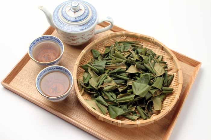 Dried loquat leaves in a basket and cups of tea on a wood tray