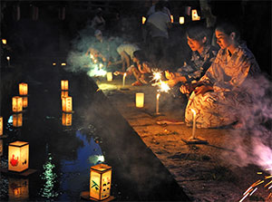 Japanese women floating lanterns in river