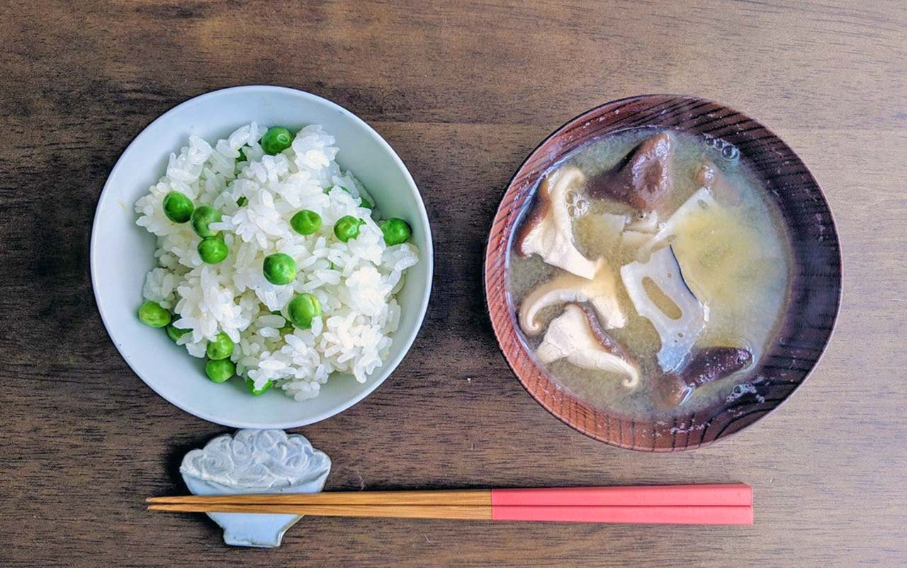 Chopsticks, a bowl of rice, and a bowl of miso soup on a wooden table