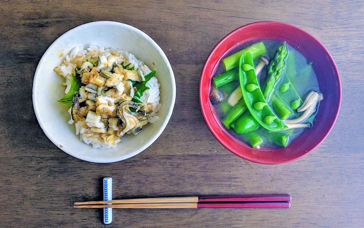 Chopsticks, grilled eel rice with snap peas, asparagus mushroom miso soup on a wooden table