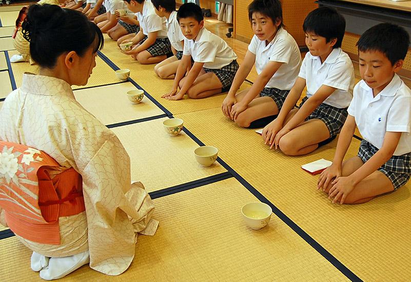 Tea sensei in kimono yeaching young boys